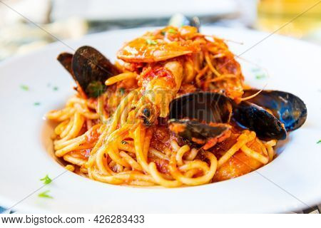 Delicious seafood pasta prepared tomato sauce, mussels and shrimps on top ready to be served in white plate.