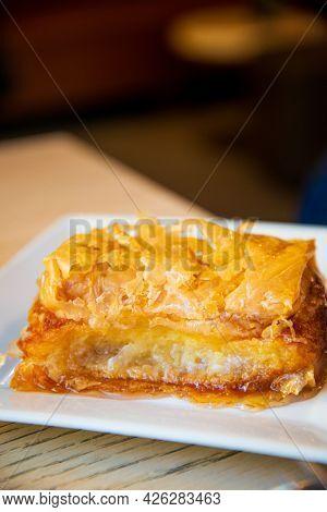 Delicious Greek sweet pastry named Galaktoboureko, made of semolina custard in filo, served with honey in white plate.