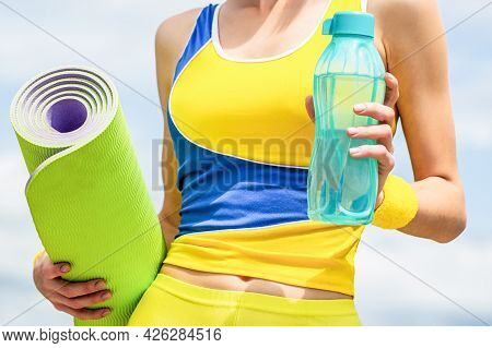 Yoga Mat And Water Bottle. Healthy Lifestyle Concept. Closeup. Fitness Girl With Yoga Mat Over Sky B