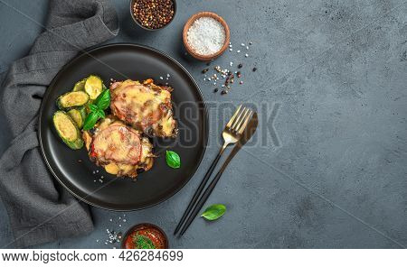 Baked Meat With Mushrooms, Tomatoes And Cheese On A Gray Background With Spices And A Linen Napkin.