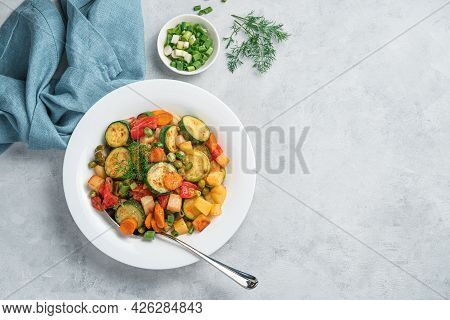 A Portion Of Vegetable Stew With Zucchini, Potatoes, Carrots And Peas On A Gray Background. Vegetari