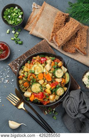 Baked Vegetables In A Frying Pan On A Gray Background With Herbs And Bread. Top View, Vertical.