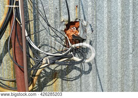 A Lot Of Tangled Wires, Cables Are Connected To Each Other, Carelessly Come Out Of A Galvanized Meta