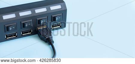 Black Usb Hub With Usb Cable Plug On Light Blue Background
