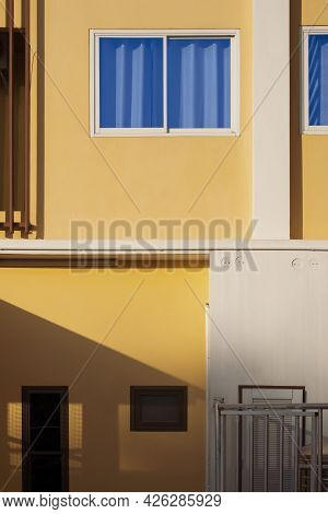 Sunlight And Shadow On Surface Of Blue Curtain In Glass Window With Storage Compartments Of Yellow H