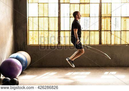 Sporty man jumping skipping rope at gym