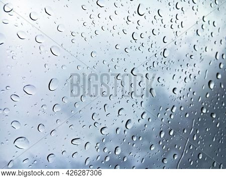 Raindrops On The Windowpane With A Gray Sky In The Background Out Of Focus - St. Gallen, Switzerland