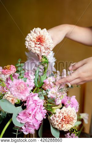 Florist arranging bouquet with pip salmon