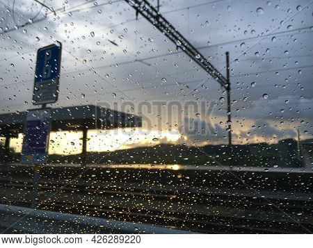 Raindrops On Car Glass With Sunset And Train Station In The Background Out Of Focus - St. Gallen, Sw