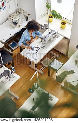 African-american Woman Designer Looks At Drawing By Sewing Machine Shooting Video In Studio