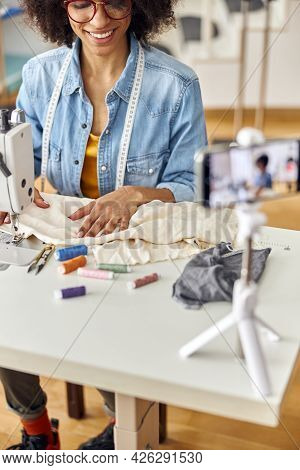 African-american Lady Designer Sews With Machine Shooting Video At Table In Studio