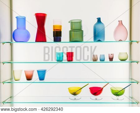 Assorted Different Sizes And Shapes Of Colorful Glassware On Shelves. Vases, Pitchers, Jugs, Glasses
