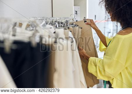 African-american Seamstress In Loose Yellow Sweater Chooses Basic Patterns In Sewing Workshop