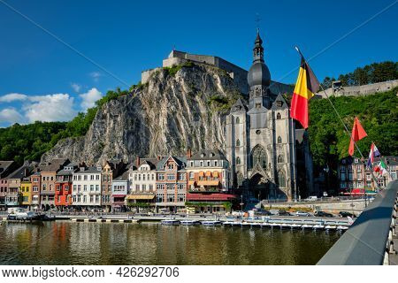 View of picturesque Dinant town, Dinant Citadel and Collegiate Church of Notre Dame de Dinant over the Meuse river with belgium flag. Belgian province of Namur, Blegium
