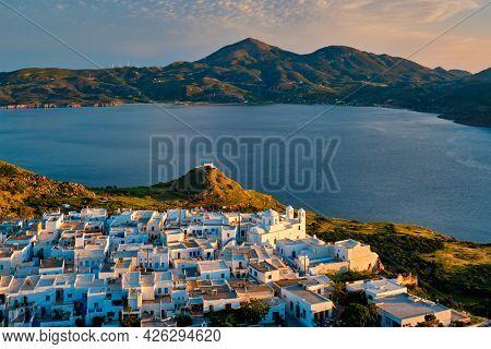 View of Plaka village on Milos island with traditional greek white houses on sunset. Plaka town, Milos island, Greece