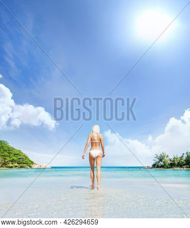 Beautiful, young and happy blond woman walking on the beach in white swimsuit. Fit and sexy fashion model in bikini. Traveling and summer resort.
