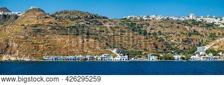 Panorama of Klima and Plaka villages with whitewhashed traditional houses and orthodox church and windmills on Milos island, Greece