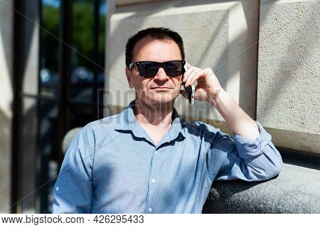 Caucasian Man Forty Years Old Businessman In The City In The Summer Talking On The Phone.