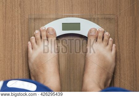 Top View Of Barefoot Male Standing On Digital Scale For Weight Control On Wooden Floor. First-person