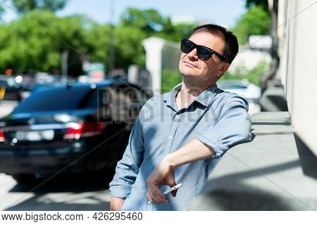 Caucasian Man Forty Years Old Businessman Near The Building In Sunglasses Is Resting.