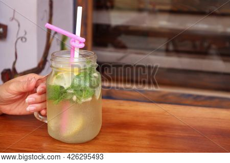 Closeup A Glass Of Mouthwatering Iced Lemonade In Woman's Hand With Selective Focus