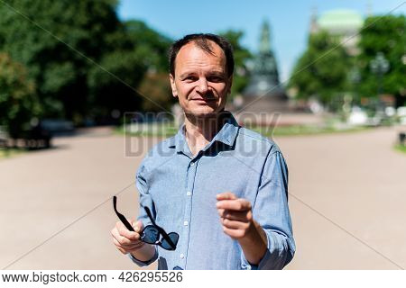 Caucasian Man Forty Years Old On The Street Greets And Smiles.