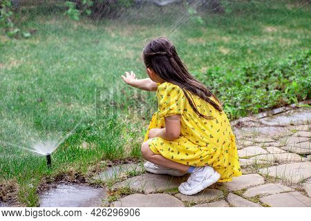 Rear View Of A Girl Who Is Playing With Water Drops From A Lawn Sprinkler, A Girl Helps Her Parents