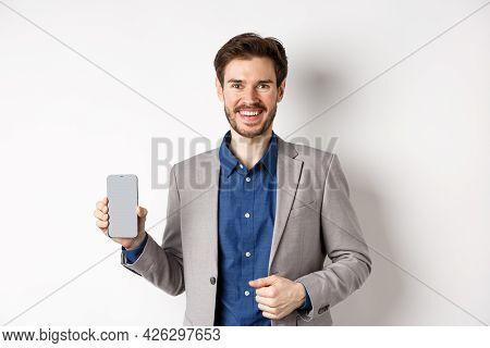 Handsome Smiling Salesman In Suit Showing Empty Smartphone Screen, Demonstrate An App, Standing On W