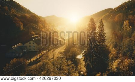 Sun over mountain village aerial. Autumn nature landscape. Sunny pine trees forest at cottages. Countryside road at mount woodland. Rural vacation at Carpathians town, Ukraine, Europe. Soft sunlight