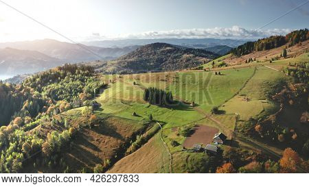Sun mountain village, cottages aerial. Nobody nature landscape at autumn. Green valley at pine trees forest. Mountaineering vacation. Carpathians mounts, Ukraine, Europe. Cinematic drone shot
