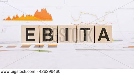 On A Light Background, Graphs, Diagrams And Wooden Cubes With The Word Ebita - Reduced Profit Before