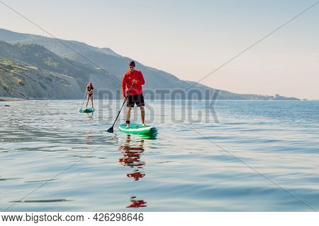 May 28, 2021. Anapa, Russia. Sporty Couple On Stand Up Paddle Board At Blue Sea. People Vacation On