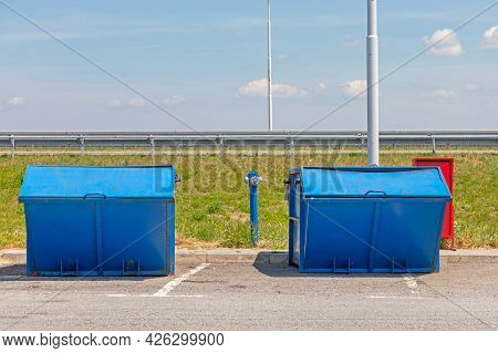 Two Big Blue Trash Dumpster Containers At Highway Stop