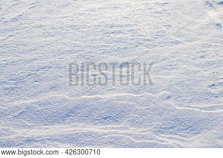 Winter Background With Snow-covered Ground After A Blizzard. Snow On The Ground In Sunny Weather