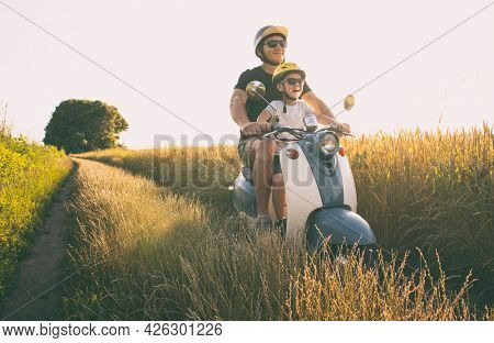 The father and son riding together through the field by pathway on the retro scooter