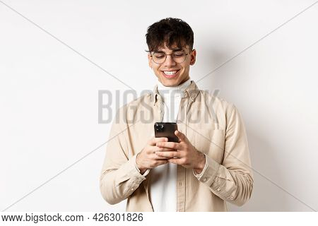 Real People. Natural Young Man Reading Message On Mobile Phone, Smiling And Looking At Smartphone Sc
