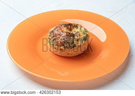 Baked Muffin-shaped Omelet On An Orange Plate.