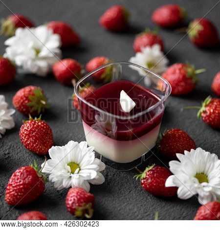 Strawberry Panna Cotta In Glass On Gray Table With Fresh Berries And White Gerbera Flowers On It. To