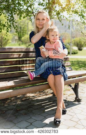 A Young Beautiful Woman And A Little Toddler Girl Are Sitting On A Park Bench. Mother And Daughter.