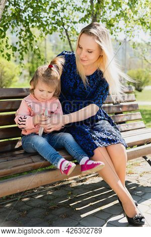 A Young Beautiful Woman And A Little Toddler Girl Are Sitting On A Park Bench And Looking At A Toy.