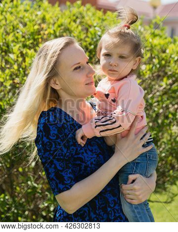 A Young Beautiful Mother Looks At Her Daughter Toddler. A Girl In Her Arms. A Sunny Day. The Happine