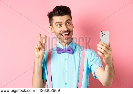 Technology Concept. Funny Man With Moustache And Bow-tie Taking Selfie On Smartphone, Showing Peace