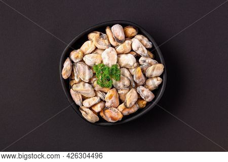 Frozen Peeled Shellfish With Green In A Black Bowl On A Dark Background, Top View.