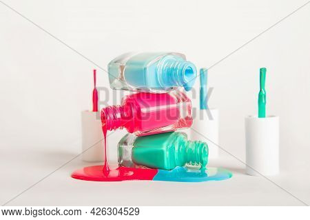 Pink, Blue And Green Nail Polishes Spill Over White Background And Copy Space. Nail Care Concept, Ge
