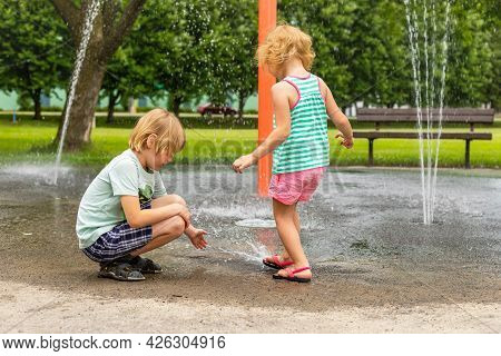 Little Children Playing At Water Splash Pad Fountain In Park Playground On Hot Summer Day.