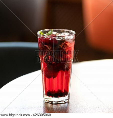 Backlit Red Iced Drink. Glass On Table, Blurred Background. Healthy Fresh Berries Juice Or Soft Drin