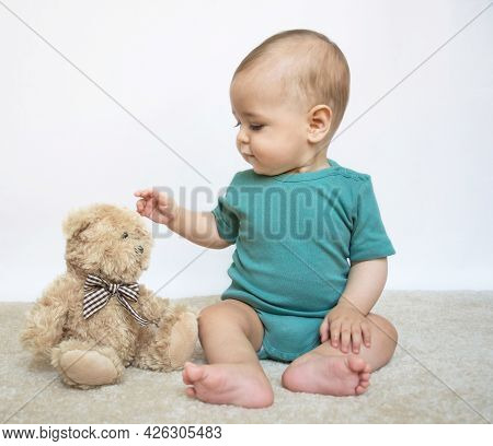 Sweet Little Baby Boy Portrait With His Little Teddy Bear On White Background
