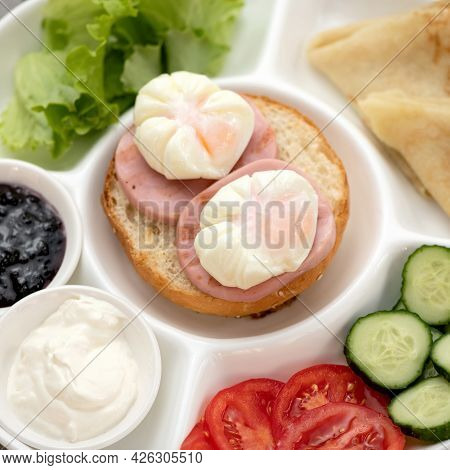 Sandwich With Sausage And Poached Eggs On White Portioned Plate With Vegetables And Sauce. Classic E