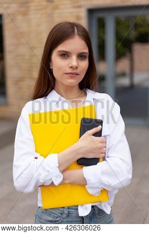 Shy Student. Portrait Of A Pretty Woman With A Folder In Her Hands Outdoors. Trainee, First Day At W