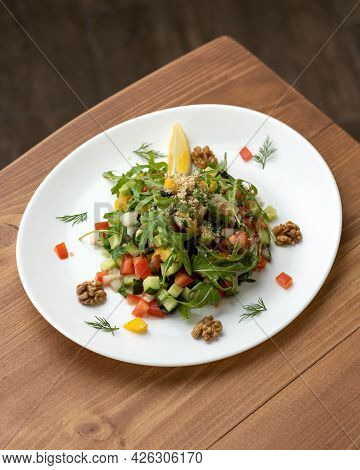 Platter With Raw Cucumbers, Tomatoes, Arugula And Walnuts On Wooden Table. Vitamin Mixed Salad Of Fr